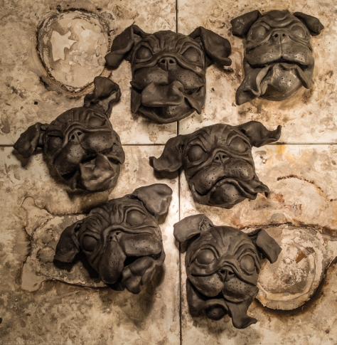 Ceramic pugs in varying stages of drying, soon to be painted.